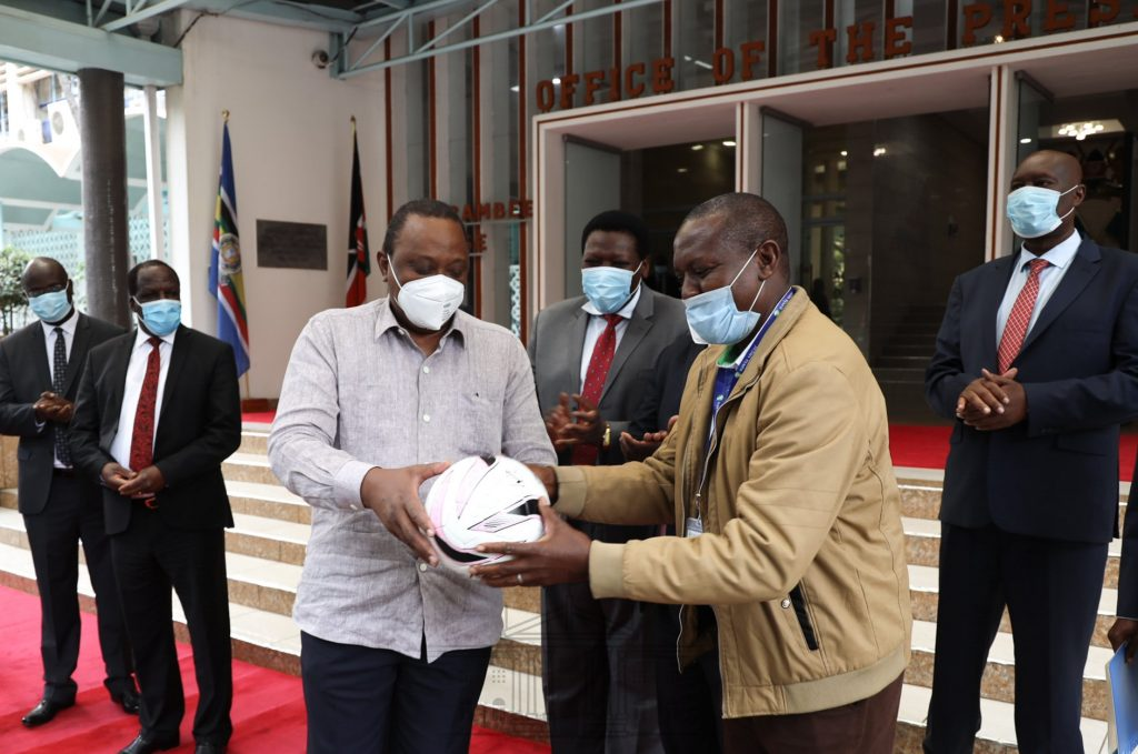 President Kenyatta signing a ball after donating a bus and 2 million shillings to Nzoia Sugar Factory.