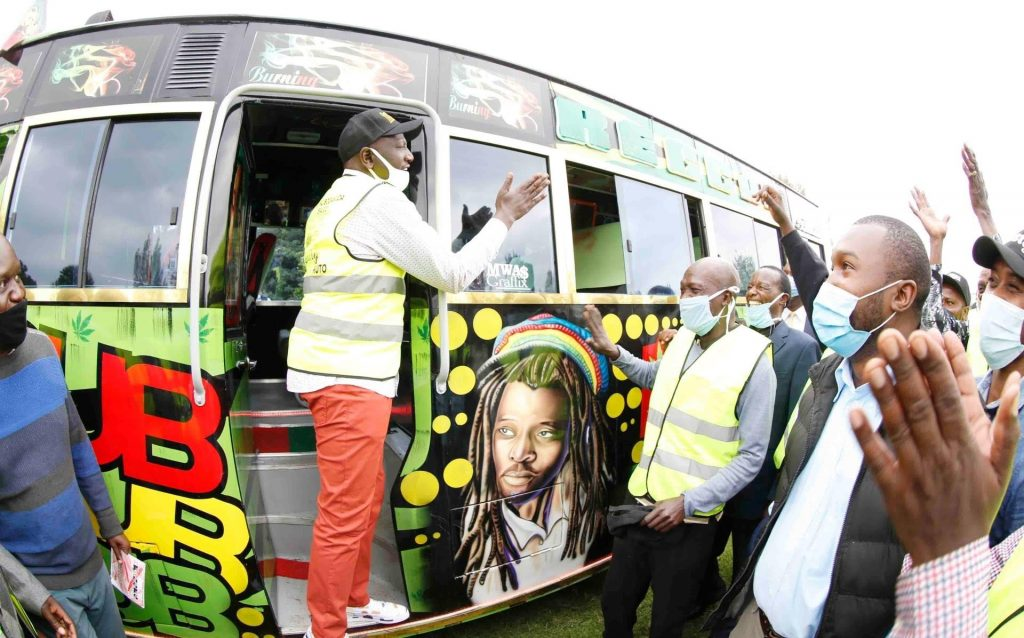 William Ruto talking while at entrance to a matatu in which he donated to Kajiado Youth Sacco. Also in attendance is Gatundu South MP Moses Kuria